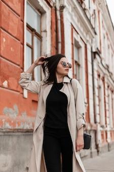 Молодая довольно крутая красивая модель женщины в модных солнцезащитных очках в модном бежевом плаще гуляет возле старинного здания в городе. милая девушка наслаждается прогулкой по улице. весенняя модная одежда для женщин.
