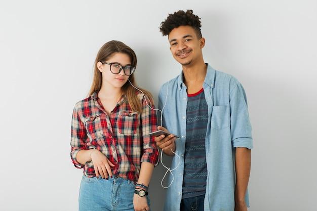 Молодая симпатичная пара, красивый темнокожий мужчина, красивая девушка, очки, изолированные, молодежь, хипстерский стиль, студенты, друзья вместе, счастливые улыбки, держащие смартфон, слушающие музыку в наушниках
