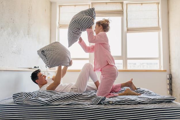 Giovani belle coppie che si divertono sul letto la mattina stanno insieme a casa da soli