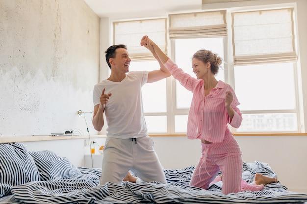 朝のベッドの上で楽しんで若いきれいなカップルが一人で家に一緒に滞在します。