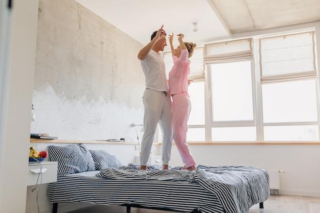 Молодая красивая пара веселится на кровати утром, оставаясь вместе дома одна