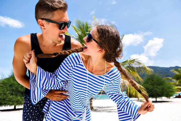 Молодая симпатичная пара молодых путешественников, весело проводящих время в тропических романтических каникулах, отдыхах на райском острове, летнем отдыхе. смотрятся друг на друга и улыбаются.
