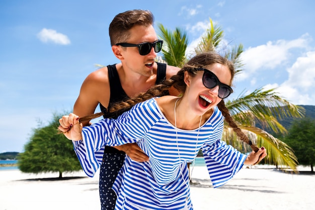 Молодая симпатичная пара молодых путешественников, весело проводящих время в тропических романтических каникулах, отдыхах на райском острове, летнем отдыхе.