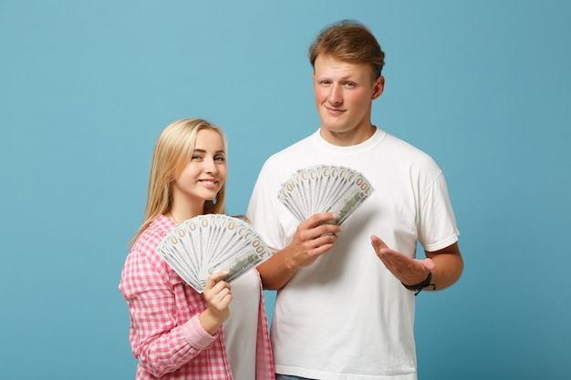 Young pretty couple two friends guy and woman in white pink t-shirts posing