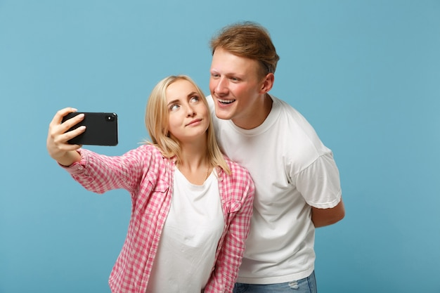 Young pretty couple two friends man and woman  in white pink empty blank t-shirts posing