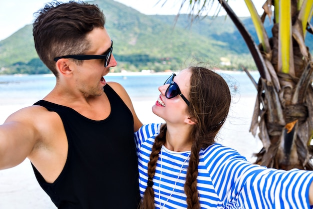 Young pretty couple of young travelers having fun and making selfies in tropical vacation