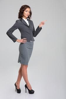 Молодая довольно кудрявая счастливая улыбающаяся женщина в формальной одежде и туфлях на каблуках, указывая в сторону на copyspace