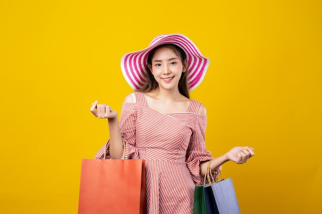 Young pretty cute asian woman holding shopping bags in both hands with smiley face standing in studio.