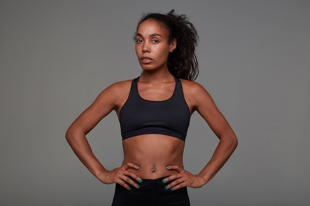 Young pretty dark skinned curly lady with belly button piercing holding hands on her waist while posing in athletic black clothes