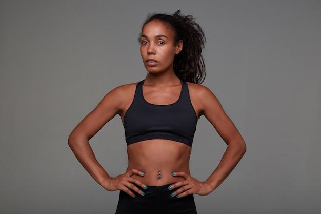 Молодая довольно темнокожая кудрявая дама с пирсингом в пупке, держась за руки на талии, позирует в спортивной черной одежде