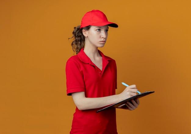 Молодая красивая доставщица в красной форме и кепке держит буфер обмена и ручку, смотрит прямо и готовится писать, изолированные на оранжевом фоне с копией пространства