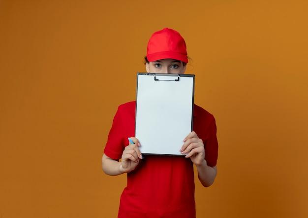 Молодая красивая девушка доставки в красной форме и кепке держит ручку с буфером обмена и смотрит в камеру из-за буфера обмена, изолированного на оранжевом фоне с копией пространства