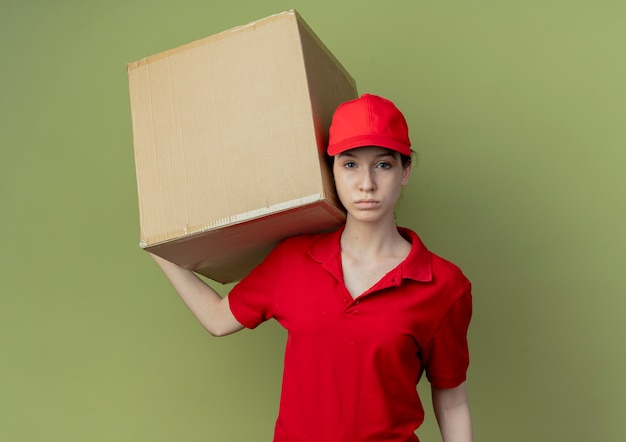 Young pretty delivery girl in red uniform and cap holding carton box on shoulder and looking at camera isolated on olive green background with copy space