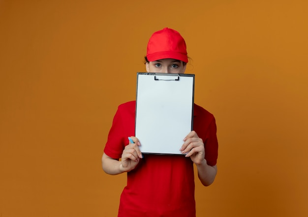 Young pretty delivery girl in red uniform and cap holding clipboard pen and looking at camera from behind clipboard isolated on orange background with copy space
