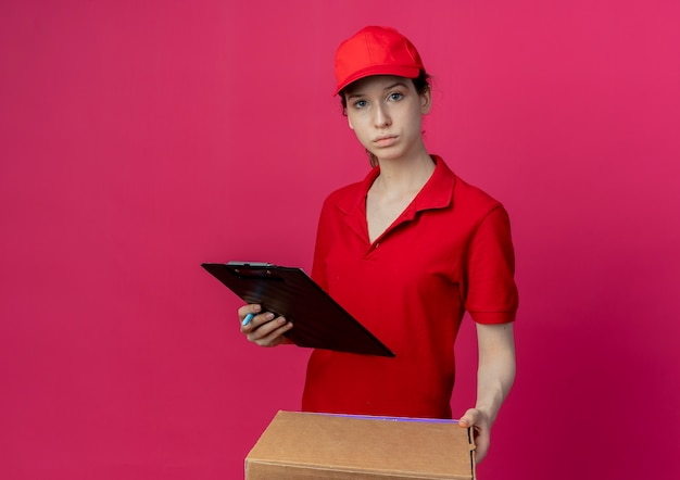 Young pretty delivery girl in red uniform and cap holding pizza package and clipboard looking at camera isolated on crimson background with copy space