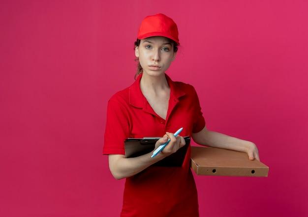 Giovane ragazza graziosa di consegna in uniforme rossa e cappuccio che tiene la penna e la lavagna per appunti del pacchetto della pizza che esaminano macchina fotografica isolata su fondo cremisi con lo spazio della copia
