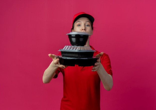 Young pretty delivery girl wearing red uniform and cap looking at camera stretching out food containers at camera isolated on crimson background with copy space