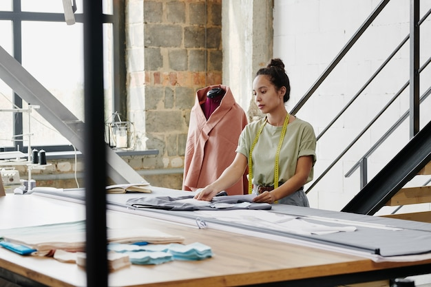 Young pretty designer of clothes in casualwear standing by large table in her studio or workshop and looking through new sketches