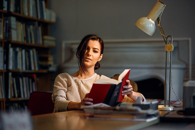 Young pretty and enthusiastic student girl reading book in university library under a table lamp