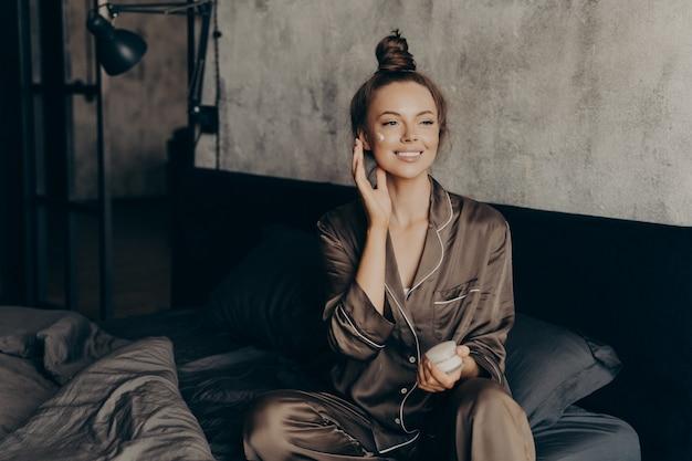 실크 파자마를 입은 젊은 예쁜 유럽 여성이 집에서 아침에 일어나 보습 페이스 크림을 바르고 일을 준비하면서 피부와 몸을 관리합니다. 미용 및 스킨 케어 컨셉