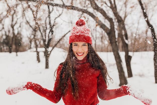 雪の中で公園で遊んで、暖かい服を着て、楽しんで、赤いミトンとニットのセーターを着て歩いている帽子をかぶった若いかなり興奮した率直な笑顔の幸せな女性