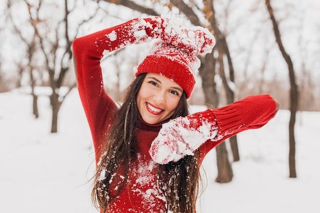Молодая довольно возбужденная откровенная улыбающаяся счастливая женщина в красных варежках и шляпе, носящая вязаный свитер, гуляет, играя в парке в снегу, теплой одежде, веселится