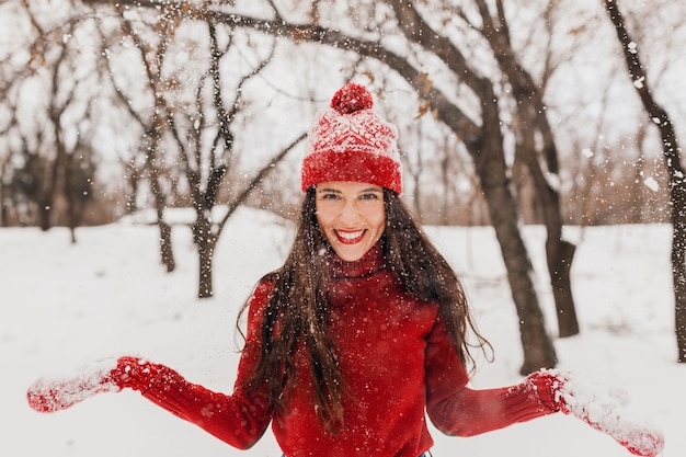 Giovane donna felice sorridente candida piuttosto eccitata in guanti rossi e cappello che indossa maglione lavorato a maglia a piedi giocando nel parco nella neve, vestiti caldi, divertendosi