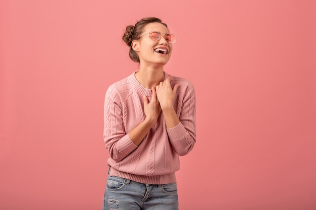 Young pretty exited laughing woman in pink sweater and sunglasses isolated on pink studio background
