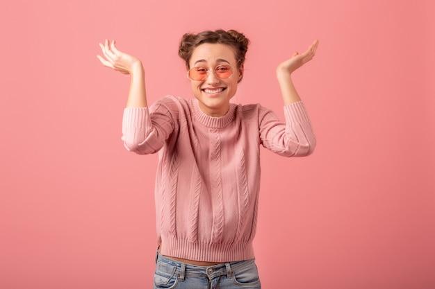 젊은 꽤 분홍색 스튜디오 배경에 고립 봄 스타일 트렌드에 분홍색 스웨터와 선글라스에 재미 있은 얼굴로 웃는 여자를 종료