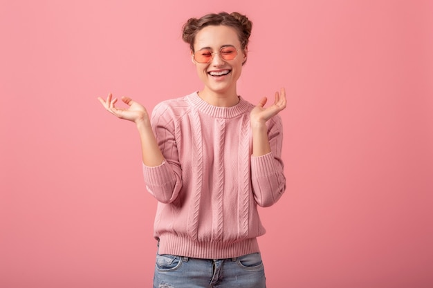 젊은 예쁜 분홍색 스웨터와 분홍색 스튜디오 배경에 고립 된 선글라스, 솔직한 미소에 진심으로 웃는 여자를 종료