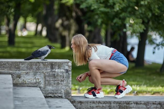 Молодая симпатичная женщина лет 20 с длинными светлыми волосами пытается поговорить с прирученной птицей в садовом павильоне.
