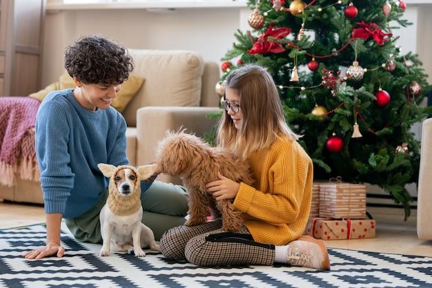 젊고 예쁜 여성과 그녀의 딸은 평상복을 입고 크리스마스 트리 옆 거실 바닥에 앉아 있는 동안 재미있는 개와 놀고 있습니다.