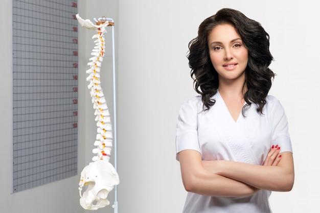 Молодой милый женский доктор в форме держа оружия пересеченный. модель искусственного шейного отдела позвоночника человека в медицинском кабинете. ортопедическая практика