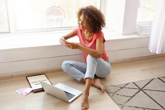 젊은 예쁜 여성 프리랜서가 현대 노트북을 사용하여 집에서 원격으로 작업하고 노트북에서 전화 번호를 검색하고 그녀의 스마트 폰으로 전화를 걸 것입니다.