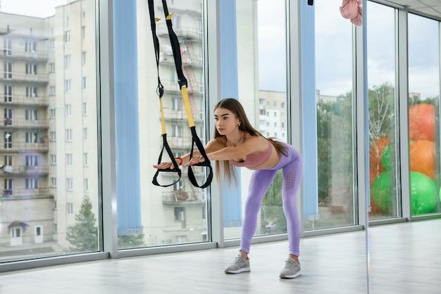 피트니스 체육관에서 trx 스트랩과 운동 상체를 하 고 젊은 예쁜 여성 강사. 건강 라이프 스타일을위한 모든 것