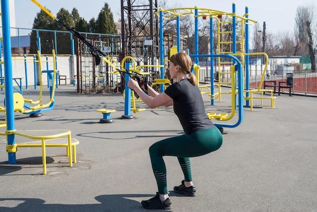 Trxストラップの練習をしている若いきれいな女性インストラクターは屋外で練習します。健康的なライフスタイルのためのすべて。