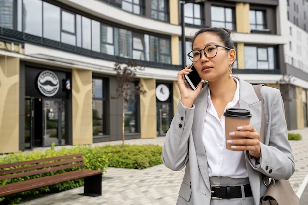 거리에서 전화하는 양복을 입은 젊은 예쁜 여성 매니저