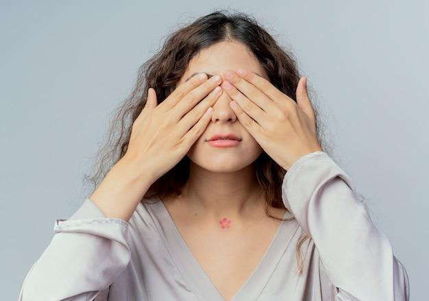 L'impiegato di ufficio femminile grazioso giovane ha coperto gli occhi con le mani isolate su bianco