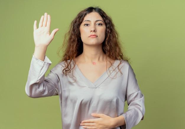 胃に手を置き、オリーブグリーンの壁に隔離された停止ジェスチャーを示す若いきれいな女性サラリーマン