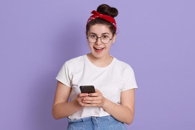 Молодая симпатичная женщина стоит изолированно над фиолетовым пространством и мило улыбается во время чата с друзьями