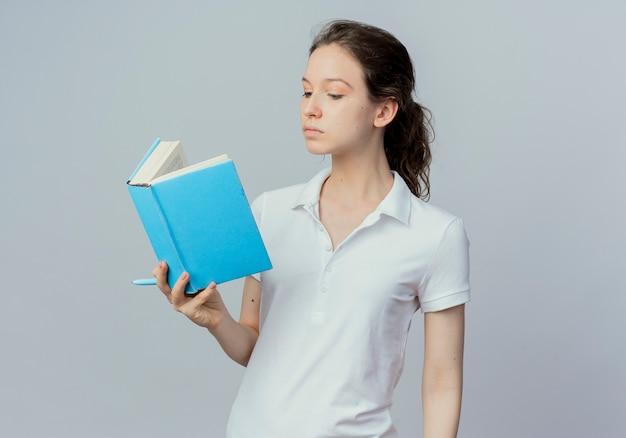 Молодая красивая студентка держит и читает книгу с ручкой в руке, изолированной на белом фоне с копией пространства