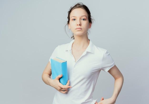 Giovane studentessa graziosa che tiene il libro e che guarda l'obbiettivo isolato su priorità bassa bianca con lo spazio della copia
