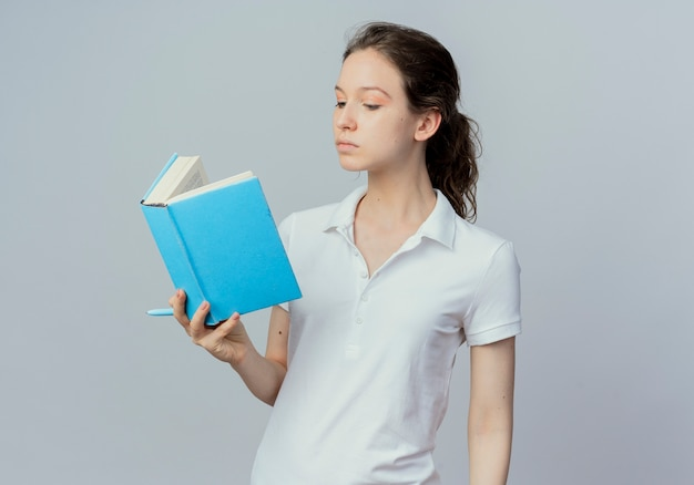 Young pretty female student holding and reading book with pen in hand isolated on white background with copy space