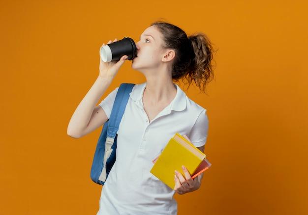 コピースペースとオレンジ色の背景に分離されたプラスチック製のコーヒーカップから本のメモ帳ペンを保持し、コーヒーを飲む側を見てバックバッグを身に着けている若いきれいな女子学生