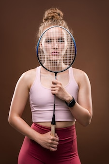 Young pretty female tennis player in pink tanktop and crimson leggins holding racket in front of her face