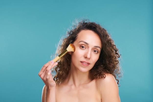 화장용 브러시로 파우더나 홍당무를 바르고 고립되어 얼굴에 화장을 하는 젊고 예쁜 여성 프리미엄 사진