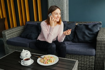 Young pretty female with good mood talking on mobile smartphone while eating salad