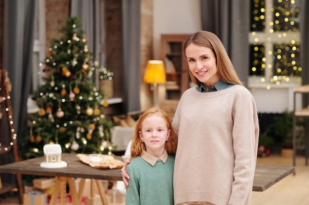 둘 다 집에서 장식 된 firtree에 대해 카메라 앞에 서있는 동안 그녀의 귀여운 작은 딸을 껴안은 이빨 미소로 젊은 예쁜 여성