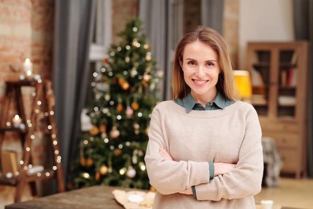 집에서 장식 된 firtree에 대해 카메라 앞에 서있는 동안 가슴에 교차하는 그녀의 팔을 유지하는 이빨 미소로 젊은 예쁜 여성