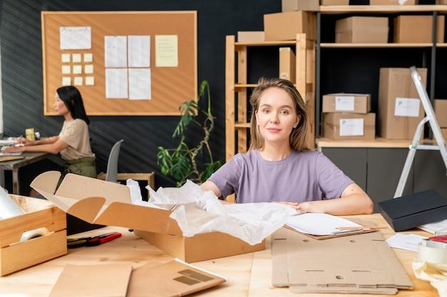 Молодая симпатичная женщина-работник офиса интернет-магазина сидит за столом, упаковывает заказы клиентов и проверяет данные в документе